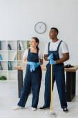 Usmívající se čistič v uniformě drží hadr u africké americké kolegyně s mop v úřadu