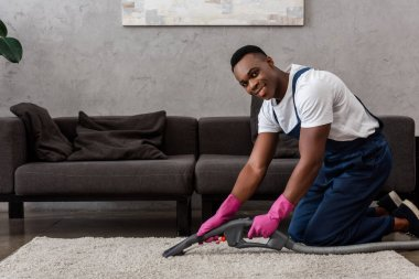 African american cleaner in uniform smiling at camera while cleaning carpet at home stock vector