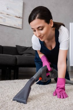 Attractive cleaner in rubber gloves and uniform cleaning carpet in living room stock vector