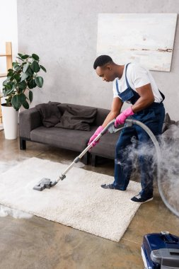 African american cleaner vacuuming carpet with hot steam in living room stock vector