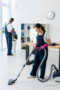 Selective focus of cleaner using vacuum cleaner near african american colleague in office stock vector
