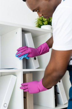 Selective focus of african american cleaner in rubber gloves cleaning cupboard near paper folders in office stock vector