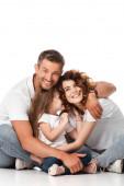 šťastná rodina s úsměvem a objímání na bílém