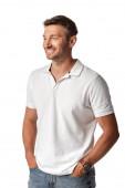 boldog férfi fehér pólóban áll a kezét a zsebében elszigetelt fehér