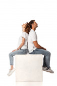 side view of couple sitting on cube and looking up on white