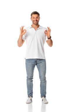 Cheerful man showing ok sign and standing on white stock vector