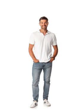 Cheerful man in white t-shirt smiling while standing with hands in pockets on white stock vector