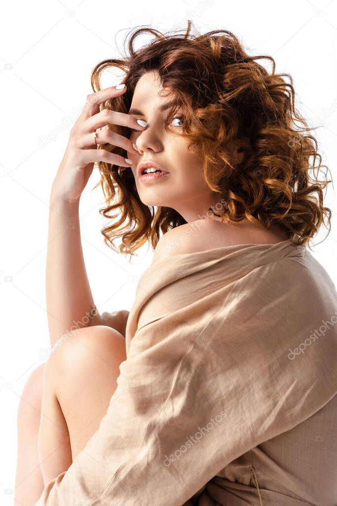 Curly and beautiful woman looking at camera and touching face isolated on white stock vector
