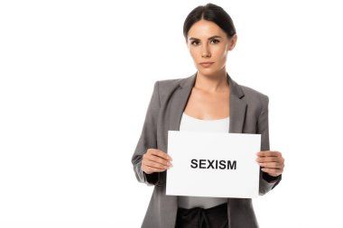 Attractive businesswoman holding placard with sexism lettering isolated on white stock vector