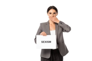 Businesswoman covering mouth while holding placard with sexism lettering isolated on white stock vector