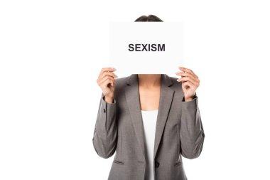 İş kadını yüzünü örterken beyaz üzerine cinsiyet ayrımcılığı yazılı bir pankart tutuyor.