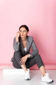 nachdenkliche Geschäftsfrau in Anzug und weißen Turnschuhen, die wegschaut, während sie auf rosa