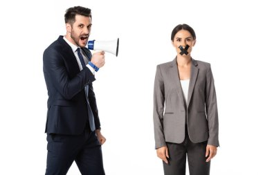 bearded businessman screaming in megaphone near businesswoman with duct tape on mouth isolated on white, gender inequality concept