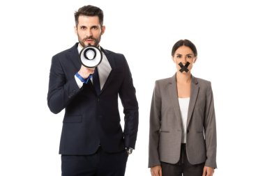 Bearded businessman standing with hand in pocket and holding megaphone near businesswoman with duct tape on mouth isolated on white stock vector