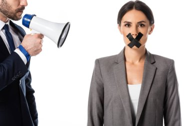 bearded businessman holding megaphone near businesswoman with duct tape on mouth isolated on white, gender inequality concept