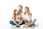 glückliche Familie sitzt mit gekreuzten Beinen auf dem Boden und umarmt isoliert auf weiß