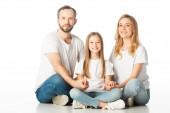 šťastná rodina sedí na podlaze se zkříženýma nohama a drží ruce izolované na bílém