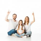 šťastná rodina sedí na podlaze se zkříženýma nohama a ukazuje nahoru izolované na bílém