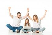 vzrušené rodiče sedí na podlaze poblíž šťastné dcery s notebookem izolované na bílém
