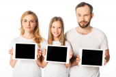 smiling family in white t-shirts holding digital tablets isolated on white