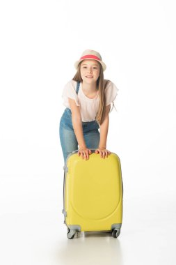 Cheerful girl in hat near yellow travel bag isolated on white stock vector