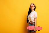 stylové letní brunetka dívka s růžovou penny palubě na žlutém pozadí