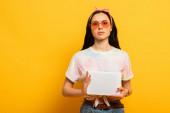 stylové letní brunetka dívka drží digitální tablet na žlutém pozadí