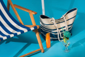 close up view of striped deck chair near sunscreen, beach bag and cocktail on blue background