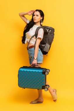 Brunette woman with backpack and suitcase looking away on yellow background stock vector