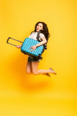 Brunette woman jumping with backpack and suitcase on yellow background stock vector