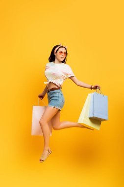 Full length view of stylish summer brunette girl jumping with shopping bags on yellow background stock vector