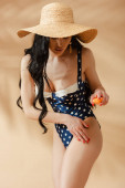 sexy brunette woman in polka dot swimsuit and straw hat applying sunscreen on beige background