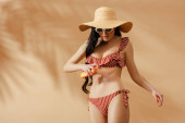 Photo sexy brunette woman in striped swimsuit applying sunscreen on belly on beige background
