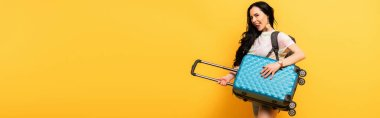 Happy brunette girl with suitcase and backpack on yellow background, panoramic shot stock vector