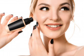 smiling naked beautiful blonde woman with makeup and black nails holding face foundation isolated on white