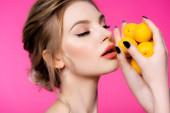 schöne blonde Frau mit geschlossenen Augen hält reife Aprikosen isoliert auf rosa