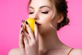 krásná blondýnka vonící zralé citron izolované na růžové