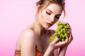 elegant beautiful blonde woman holding green grapes isolated on pink