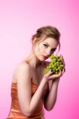 elegantní krásná blondýna žena drží zelené hrozny izolované na růžové