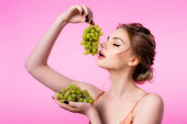 elegantní krásná blondýna žena drží zelené hrozny v blízkosti úst izolované na růžové