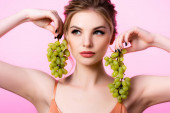 elegant beautiful blonde woman holding green grapes near face isolated on pink