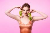 elegantní krásná blondýna žena drží zelené hrozny v blízkosti obličeje izolované na růžové