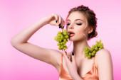 elegáns gyönyörű szőke nő eszik zöld szőlő elszigetelt rózsaszín