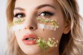 krásná blondýnka s divokými květy pod očima a v ústech izolované na bílém