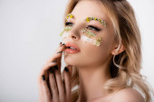 Photo naked beautiful blonde woman with wildflowers under eyes touching face isolated on white