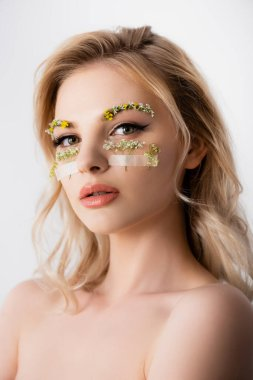 Naked beautiful blonde woman with wildflowers under eyes isolated on white stock vector