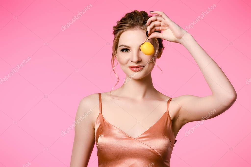 Smiling elegant beautiful blonde woman in silk dress holding apricot isolated on pink stock vector