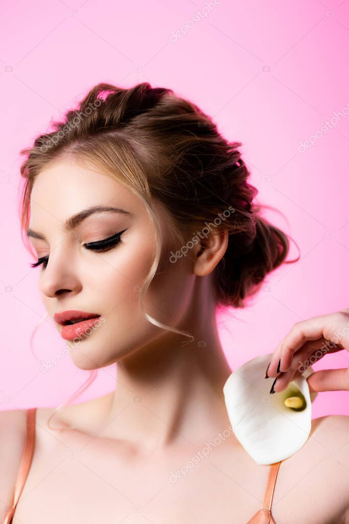 Elegant beautiful blonde woman holding calla flower on shoulder isolated on pink stock vector