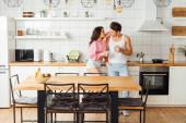 Selektivní zaměření sexy žena objímající přítele s šálkem kávy v kuchyni