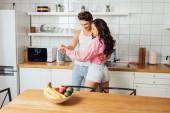 Szelektív fókusz a fiatal pár mosolygós tánc közben a konyhában